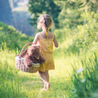 Barefoot Girl Walking In Field With Basket and Teddy Bear