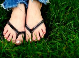 Feet Wearing Flip Flops in the Grass