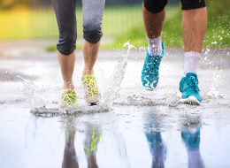 Couple Jogging Through Puddles In Bright Athletic Shoes