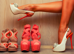 Woman Trying On Orange, Tan and White High Heels