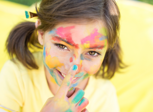 Little Girl Covered In Paint With Blue Nail Polish