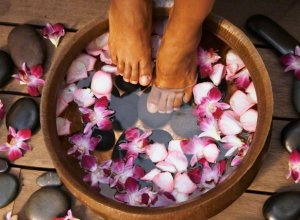 Woman's Feet In Basin Of Orchid Flower Water
