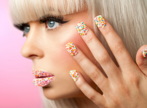 Woman With Colorful Cake Sprinkles On Her Fingernails and Lips
