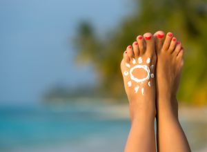 Women's Feet On The Beach With Drawing Made From Sunscreen
