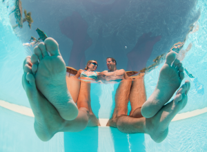 Underwater Photo Of Couple's Feet In A Pool