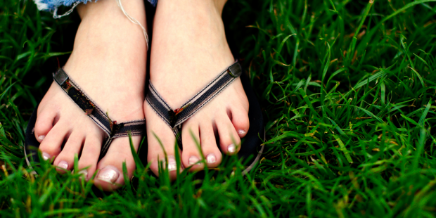 Feet Wearing Flip Flops in the Grass