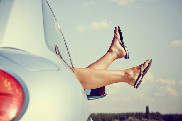 Woman Wearing Flip Flops With Her Legs Out The Car Window
