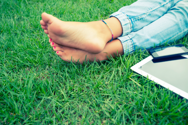 Woman's Feet In The Grass Next To A Cell Phone And Laptop