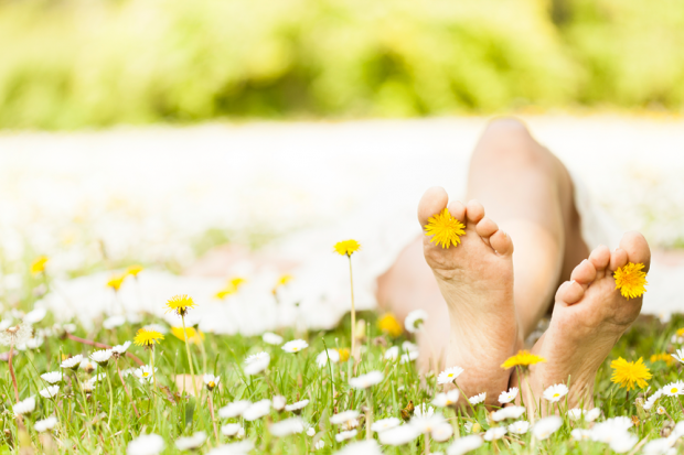 Barefoot Woman Lying In A Field Of Spring Flowers