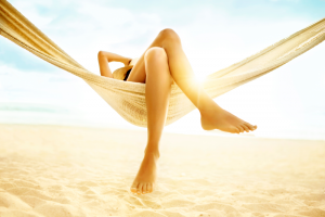 Woman with bare nails lying in a hammock on the beach