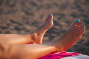 Woman Wearing Blue Toenail Polish At The Beach