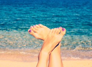 Woman With Purple Pedicure At the Beach